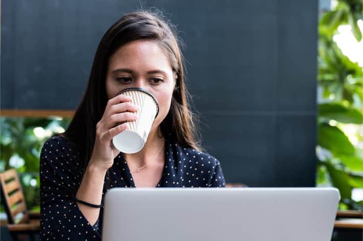 Mulher navegando no laptop e bebendo café